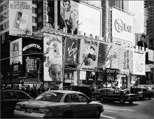 """Город соблазнов / В тени его небоскребов ,днем,авто вкл. фары,а пешеходы идут по тротуарам освещенными  огнями соблазняющей... зовущей.. рекламы (август 1998,""""мыльничка"""")"""