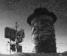 Афишная тумба, световор и дорожный знак, отражающиеся в луже на перекретке в Несвиже / как-то так