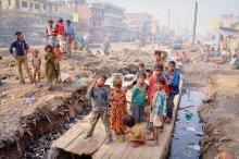 """Трущобы Патны, столицы штата Бихар / Бихар - один из самых бедных штатов Индии. Патна - столица штата - огромный милионный город с кучами мусора и кварталами трущоб прямо в центре города. Дома из битого кирпича, брезента, тряпок и картонных коробок протянулись на километры. Здесь тоже живут люди, здесь особый мир со своими радостями, своим проблемами, страданием и надеждами.. В Патне не часто бывают туристы, и уж тем более здесь, в трущобах. Кто-то смотрел с любопытством, кто-то со злобой , кто-то с удивлением.. Некоторые приглашали в гости, другие бросали камни и обливали водой, видя во мне непрошеного чужака с фотоаппаратом, пришельца из """"благополучного мира"""". А меня почему-то всегда тянуло в эти районы, к таким людям как эти. Мне всегда хотелось понять, почувствовать как и чем они живут... Когда я фотографировал этот снимок, рядом женщина чистила тухлую рыбу и мыла ее в канаве с грязной водой. Были и забавные сцены. Почти в каждой, самой бедной халупе, в брезентовой палатке есть телевизор... Нет ничего, но есть телевизор. Несколько семей из 20-ти человек, по-видимому, сбрасывались на ящик, чтобы собираться вокруг него по вечерам. И этому есть объяснение. Похоже, болливудские фильмы о жизни богатых людей с танцами и песнями - это та самая надежда и мечта, которой живут трущобы. Им нужны такие фильмы. В десятке самых популярных в Индии фильмов по итогам года никогда нет ни одного иностранного, только индийские. И, перефразируя Чехова""""если на стене в первом акте висит ружье, то в последнем оно будет петь и танцевать"""".  Когда я уходил, дети со снимка повисли гроздьями у меня на ногах и поясе с криками: """"Тен рупий"""", не давая мне уйти..Если бы я дал хоть одному из них тен рупий (десять рупий), то потом бы прибежала вся улица, а за ней весь город. Поэтому я применил старый проверенный опыт - позвал старого аксакала - патриарха трущоб, дал десять рупий ему, и тот честно отработал их, покричав на детей и помахав на них палкой, отчего я получил свободу и быстро убрался вос"""
