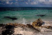 Карибы / Ласковое море резвится и играет у скалистого берега в Канкуне.