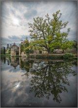 UK. Scotney Castle / Scotney Castle – английский загородный дом, окруженный садами, который расположен на юго-востоке Ламберхерста (Lamberhurst), деревни в долине реки Бьюл. Основной достопримечательностью этого места стали остатки средневекового манора, укрепленного особняка постройки XIV века, окруженного рвом, который называется Старый замок Скотни. По сути, он стоит на островке посреди крошечного озера, выполняющего роль рва. Озеро окружают разросшиеся на склонах сады с прекрасными коллекциями рододендронов, азалий и кальмий, которые цветут весной; летом приходит черед роз и глициний; а после все это разнообразие кустарников и деревьев радует глаз осенней листвой.   источник: http://united_kingdom.worlds.ru/articles/united_kingdom_article_7990.shtml официальный сайт: http://www.nationaltrust.org.uk/scotney-castle/