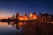 В час когда зажигаются звезды / По летописной легенде, великий князь литовский Гедимин после успешной охоты обнаружил прекрасное место недалеко от города Кернаве, решил воздвигнуть на нём замок и перенести сюда столицу. Во второй половине XIV века здесь, в Старых Троках, уже стоял каменный замок. Правил им в 1337—1382 сын Гедимина трокский князь Кейстут. Около 1350 года в этом замке родился Витовт. В 1375 году Кейстут перенёс свою столицу из Старых Трок в защищённые озером Новые Троки, где был построен Полуостровной замок. Замок в Старых Троках в 1391 году был разрушен и больше не восстанавливался. Участок земли с остатками замка Витовт в 1405 году подарил монахам бенедиктинцам. Монастырь стоит на старом замчище. Трокский Полуостровной замок был построен Кейстутом в 1370-е годы. Он был разрушен во время междоусобиц 1382—1383 годов и вновь отстроен лишь в конце правления Витовта. Трокский Островной замок был окончен в 1409 году. Он был мощнейшим и наиболее величественным во всем Великом Княжестве Литовском. Это была одна из самых неприступных крепостей во всей Восточной Европе: ни разу за всю историю врагам не удалось его завоевать. Островной замок сразу стал основной резиденцией великого князя Витовта. После Грюнвальдской битвы 15 июля 1410 года замок утратил своё военное значение, так как основной противник Великого княжества Литовского — Тевтонский орден — был разгромлен. В это время замок переживал период своего расцвета. Роскошные приемы и пиры устраивались в честь иностранных послов и высоких гостей, съезжавшихся в замок со всей Европы. В Островном замке 27 октября 1430 года умер Витовт. К концу XVI века Троки постепенно отступают на задний план в политической жизни страны. Расположенность вдали от главных торговых путей привела город к экономическому упадку. Вскоре Троки становятся местом ссылок неугодной знати, а замок использовался как тюрьма. После войны с Москвой 1655—1660 годов развалины заброшенного замка постепенно разрушались.