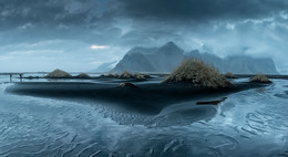 Туманный Стоккснес (панорама) / Говорят, в Исландии переменчивая погода. Напротив, этой зимой в феврале она была очень стабильная: шесть из девяти дней поездки шел дождь с перерывами на 10-30 минут. Нарядные, ослепительно белые поля и горы, искрящийся снег под низким солнцем - все сказочные виды смыло дождем. Явилась другая Исландия - туманная, преждевременно разбуженная от зимней спячки, с взлохмаченной бурой прошлогодней травой. Но все равно прекрасная.