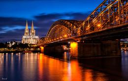 Город зажигает огни / В 1164 г. император из династии Гогенштауфенов Фридрих Барбаросса принес в дар кёльнскому архиепископу Райнальду Дассельскому мощи трёх волхвов, привезённые им в Кёльн из Милана. С тех пор в город стекались паломники со всей Европы для поклонения реликвиям волхвов. Паломничество к мощам волхвов играло существенную роль как в религиозной, так и в экономической жизни Кёльна. Короны трёх волхвов по сей день украшают городской герб.