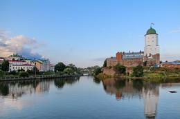 Выборгское утро / Когда-то давно, по дороге в Финляндию, в утренних лучах майского солнца я увидела прекрасный замок. Прошло много лет, и я побывала в нём. Стоит он на Замковом острове, окруженный водой. Белая башня Святого Олафа словно вырастает из гранита и вонзается в глубокую синеву северного неба. Это — единственная в нашей стране полностью сохранившаяся крепость европейского типа. Это — Выборгский замок.