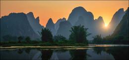 Вечер в Гуанси / Провинция Гуанси (Гуанси-Чжуанский автономный район) — регион на юге-западе Китая, который обычно начинается с посещения этого уютно расположившего между карстовыми скалами города Гуйлинь. Для туристов этот район был открыт в 70-х годах и теперь является одним из самых посещаемых мест в Китае. Популярность городу Гуйлиню создал неповторимый сказочный пейзаж – огромное число известковых скал мистической формы, утопающих в тропической зелени