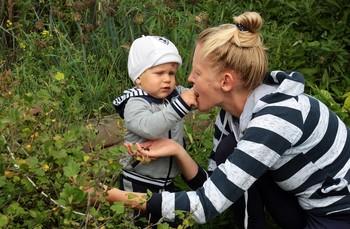 Кормилица мамы / Ребёнок кормит ягодками маму.