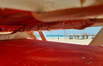 майский пляж сквозь сложенные лежаки / Тель-Авив, май 2021 года.