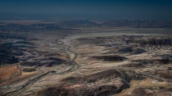 Отджинджанге и горы Хартманна / Сухое русло реки Отджинджанге пролегает среди горного массива Хартманна на Северо-Западе Намибии. Это безводная местность, лишенная жилья и дорог. Жизнь здесь застыла в ожидании дождя, которого не было несколько лет.